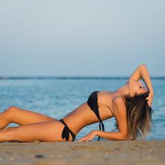 Sexy woman wearing bikini posing at the beach.