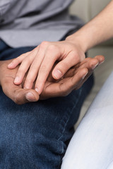 Close up of couple holding hands while sitting.