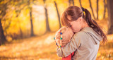 mother sharing love with daughter at fall forest poster