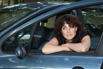 femme en attente à l'avant de son véhicule