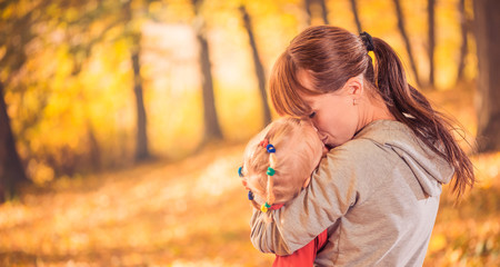 mother sharing love with daughter at fall forest