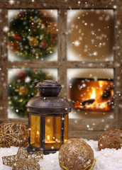 Christmas lantern and ornaments on snow in front of a window
