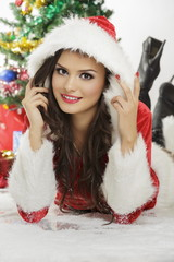 Smiling pretty lady in Santa Claus costume with hood lying down