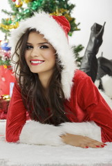 Smiling pretty lady in Santa Claus outfit with hood lying down