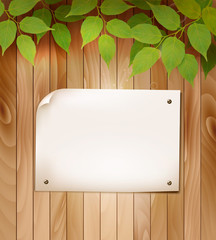 Natural wooden background with leaves and a blank piece of paper