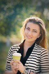 Woman holding hot beverage enjoying nature