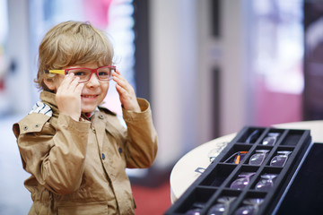 Cute little kid boy at optician store during choosing his new gl