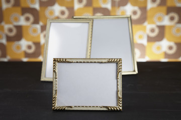 Blank picture frames against kitsch background