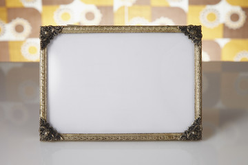 Blank picture frame against kitsch background