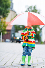 Cute little boy with yellow umbrella and colorful jacket outdoor