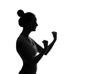 Silhouette of young woman with raised fists