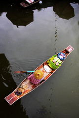 Wooden boat vendor in canal at Thaka Floating Market, Thailand.