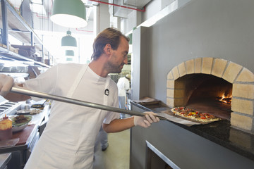Chef placing pizza in brick oven
