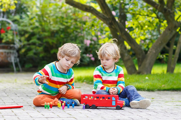 Two little brother boys playing with red school bus
