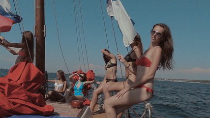 Beautiful girls having fun and dancing on a yacht with red sails