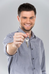 Businessman holding key with focus on key.