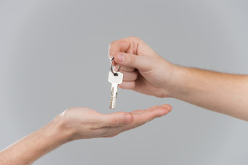 Male hand holding key and handing it over to another person.
