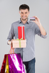 man holding bagsand boxes with credit debit card.
