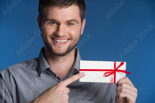 Present gift in hands of smiling man. - 71593608