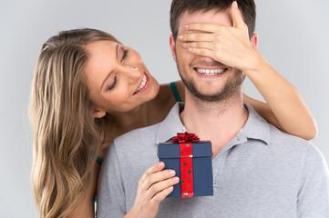 romantic woman covering her boyfriend's eyes.