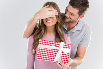Man surprising his girlfriend with gift on grey background.
