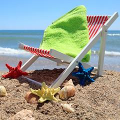 Beach chair near the ocean with shells