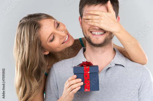 Leinwandbild Motiv romantic woman covering her boyfriend's eyes.