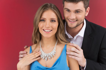 Closeup on man looking at necklace on girl's neck.