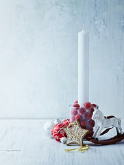 White candle and vintage Christmas decorations
