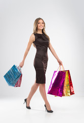 Shopping woman walking with bags isolated on white background.
