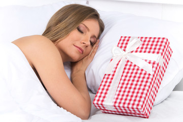 Asleep woman has surprise present waiting for her in bed.