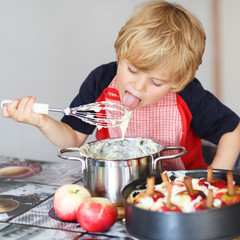 Adorable little boy helping and baking apple pie in home''s kitc