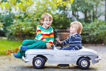 Two happy kids playing with big old toy car in summer garden, ou
