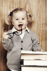 Portrait young girl in glasses next to books