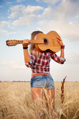 girl with a guitar on a background of a wheat field