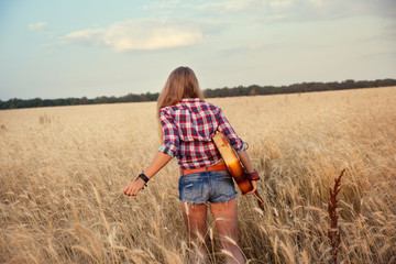 slender girl with a guitar running through the wheat field
