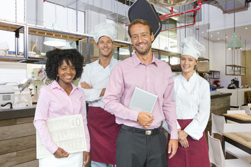 Business owner with chefs and waitress in restaurant