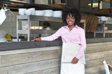 Smiling waitress holding menu in restaurant