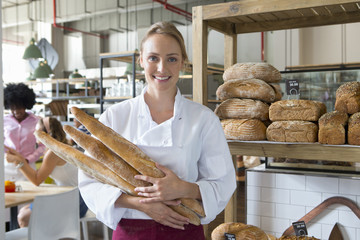 Smiling baker holding bread in bakery
