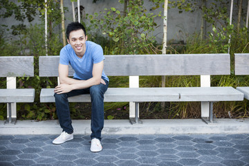 Happy young asian man on bench