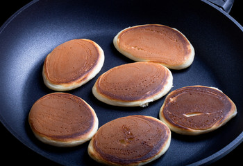 six pancakes in a frying pan