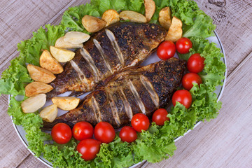 Whole grilled fish carp served with potatoes, tomatoes and salad