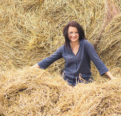 young beautiful girl on a background of haystack