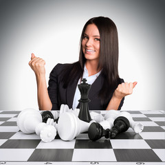 Joyful businesswoman wins chess and raised his hands up