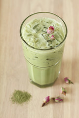 glass of green tea latte with dried rose on wooden background