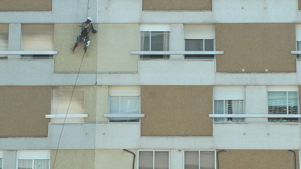 Industrial climbers work in facade of building