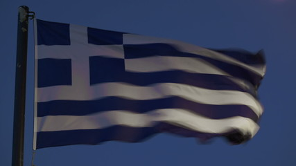 Greek flag fluttering against evening sky