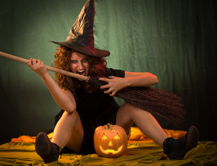 Woman dressed like a witch. She is with broom and pumpkin.