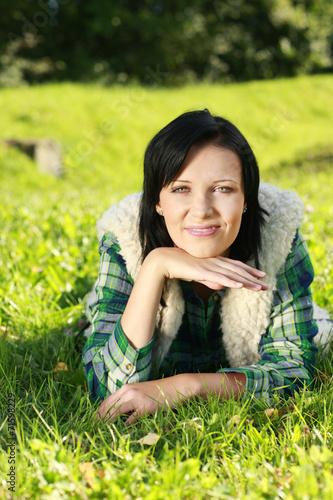 canvas print picture Junge Frau liegt im Gras