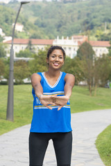 Beautiful smiling sporty woman doing stretches before training a